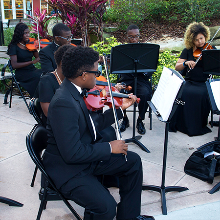 Young adults playing their violins outside