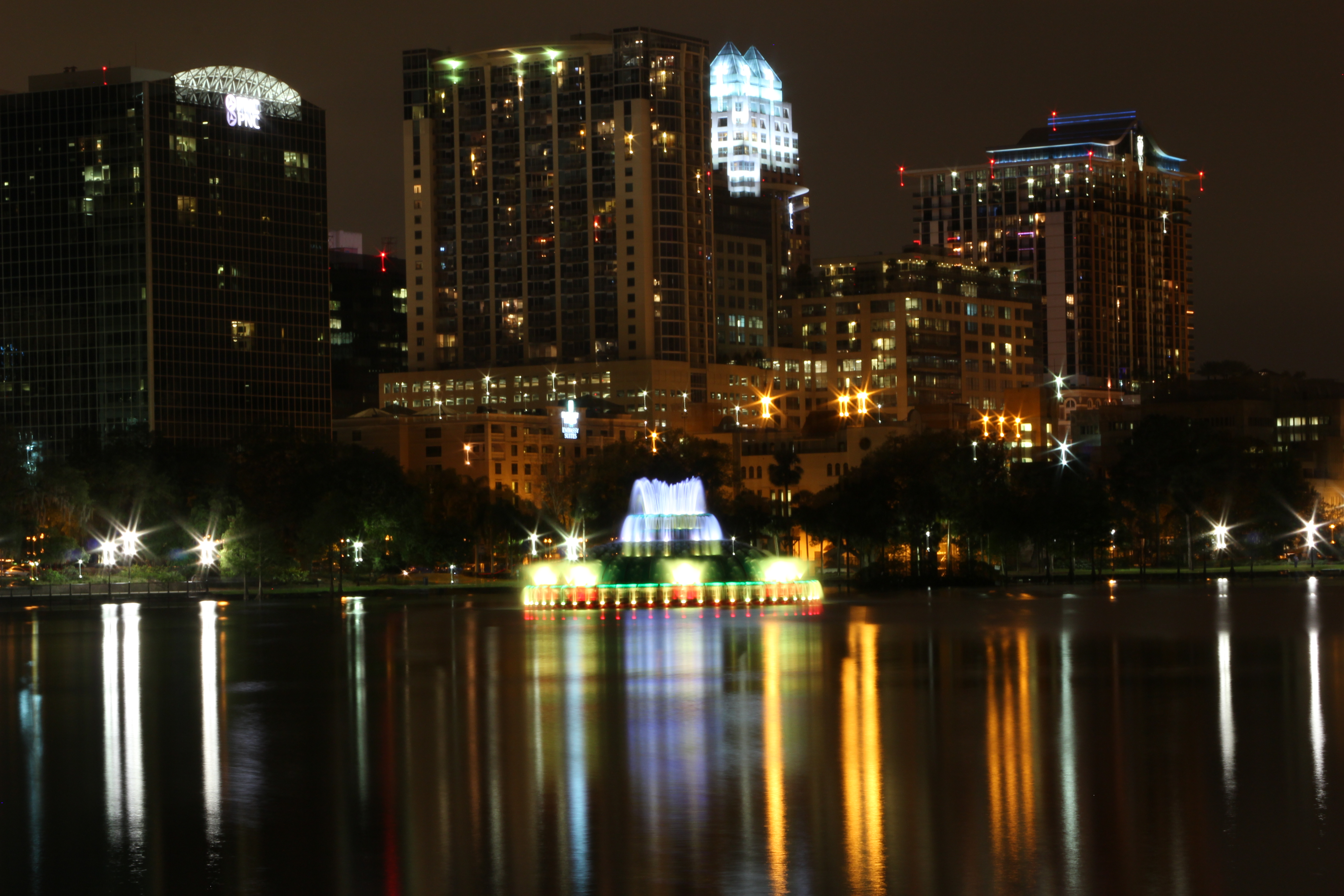 Photograph of the Lake Eola fountain with the Orlando skyline in the background, at night