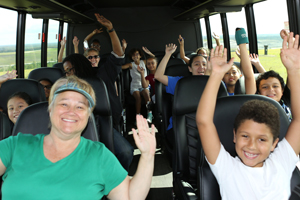 Adults and children raise their arms in celebration on the landfill tour bus at the 2018 Orange County Recycles Day event.
